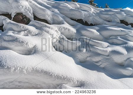 Snow on rocks with lines and designs as well as texture and beauty