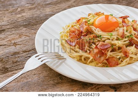 Spaghetti carbonara with bacon, cheese, yolk and sprinkle chopped parsley. Delicious spaghetti carbonara on wood table in side view with copy space. Italian traditional homemade food for lunch or dinner. Spaghetti carbonara ready to serve.