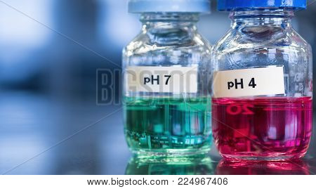 pH 7 (green) and 4 buffer (red) solutions in glass bottles. Labels separately printed and adhered. These calibration solutions are commonly found in science laboratories where meters are used to measure sample acidity or alkalinity.
