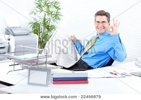 Mature business man reading newspaper in modern office.