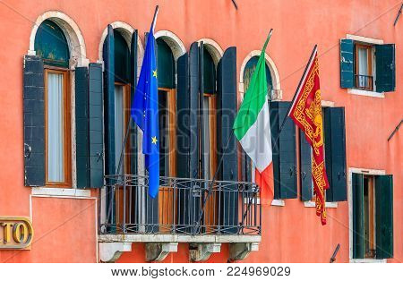 Facade of a typical old building with shutters and ornate windows, the Italian, the European and the Venitian flags in Venice, Italy