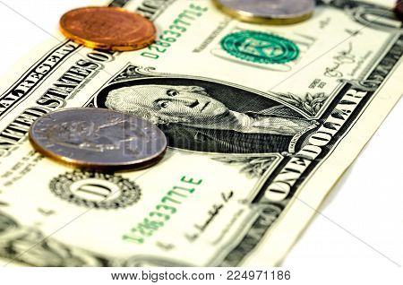 close up of a a dollar bill with cent coins over a white background. symbol of wealth