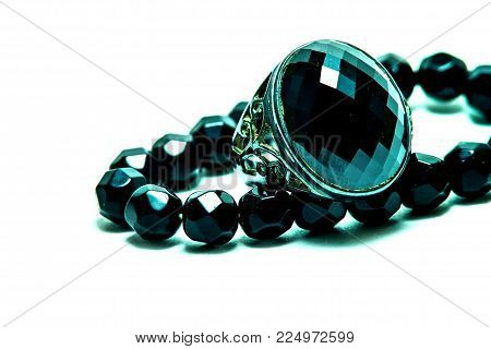 Sapphire ring with onyx bead necklace on white background