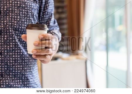 close up of man hands holding cup of coffee