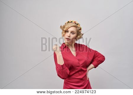 young beautiful blond woman in red dress with evil, serious , threatening expression shows her fist and threatens trouble. An annoyed expression. The concept of education, warning, admonition