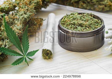 Joint and a grinder with crushed weed Leaf of cannabis, buds of marijuana, unrolled weed on a white background top view close