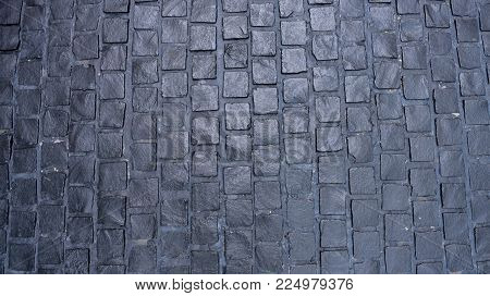 Black cobbled stone road background with reflection of light seen on the road. Black stone pavement texture. Ancient paving stone background