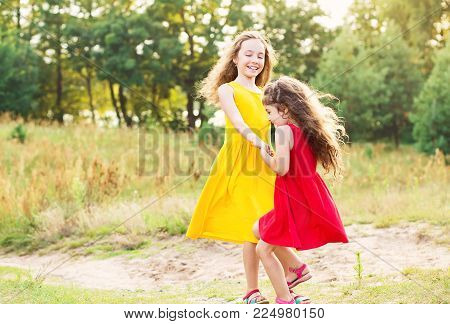 Two Happy little girl embracing and dancing at sunny summer day
