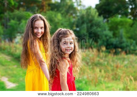 Two beautiful little girsl embracing and smiling at sunny summer day. Happy childhood concept