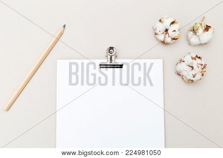 White sheet for writing with pencil and cotton flowers on a gray background. Mock up