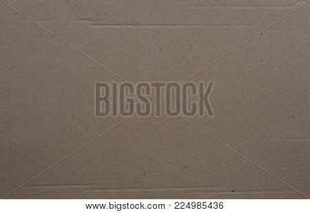 Brown cardboard paper background. Craft paper closeup photo. Rough grungy paper for drawing. Taupe toned carton. Wrapping paper for post parcels. Shipment and delivery banner template. Blank card