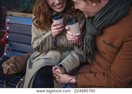 Glad man and woman are enjoying date outdoor. They are holding hands and smiling while drinking hot beverage