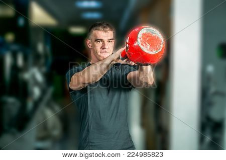 Gym training. Muscular and strong man in sweat kettlebell workout in the gym, selective focus