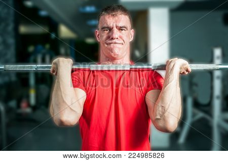 Gym training. Strong muscular man with muscles performing weightlifting training sport with heavy metal barbell weight and hard face expression