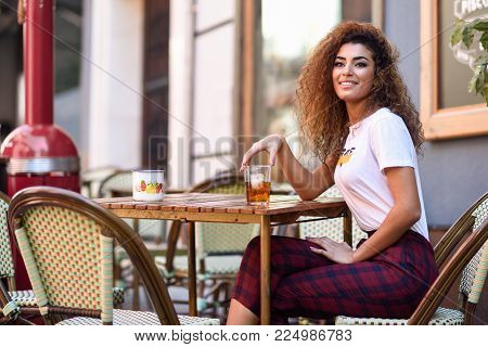 Arabic Smiling Woman In A Beautiful Bar Looking At Her Smartphone