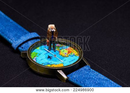 Senior age backpacker and world map watches. Around world travel photo banner. Senior traveler figurine. Retired backpacker travel. Lifetime traveller. Travelling around world concept. Aged traveler