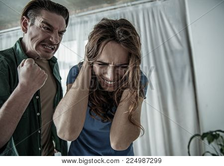I will hit you. Mad husband is threatening his wife by fist. Terrified lady is closing her head with fear