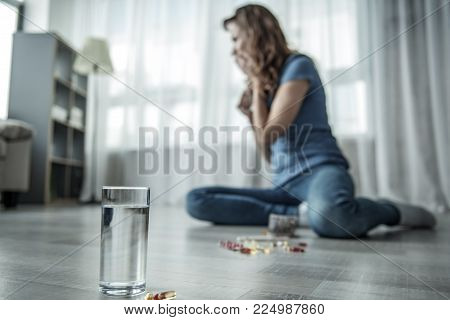 Stressful young woman wants to commit suicide. She is sitting on floor and crying. Focus on glass of water and drugs