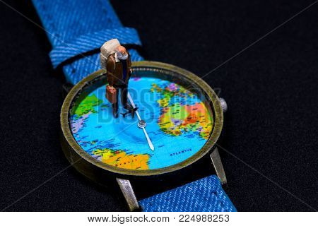 Old tourist in backpack and world map watches. Around world travel photo banner. Senior traveler figurine. Retired backpacker travel. Lifetime traveller. Travelling around world concept. Aged traveler