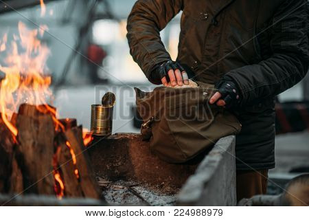 Stalker, male person warms his hands on fire