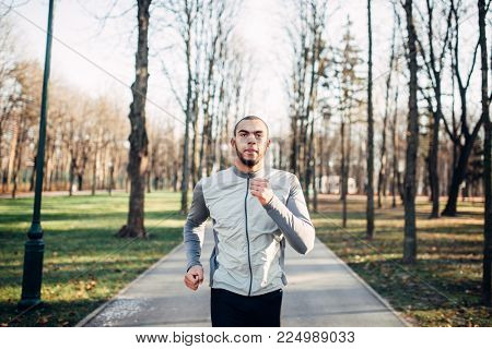 Jogger in motion, running in autumn park