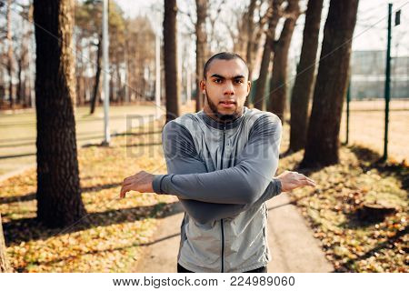 Male jogger on fitness workout in autumn park
