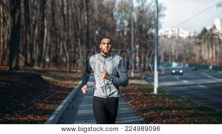 Male runner in sportswear on training outdoor