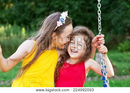 Two happy beautiful girls sitting on seesaw and smiling at warm  summer day
