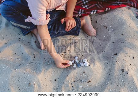 A child playing cockleshells on the beach sitting on a red plaid plaid