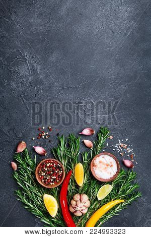 Spices and herbs on black stone table top view. Ingredients for cooking. Food background.