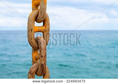 Chain and blue sea. Yellow mooring chain of cargo ship. Commercial shipment by sea. Seascape with ship chain. Sea landscape from dock. Summer vacation cruise concept. Travel by sea banner template