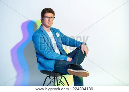 Portrait of calm male locating on seat while looking at camera. Multicolored shadow. Composure concept