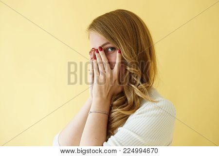 Body language. Portrait of fashionable young lady with blonde curly hair making terrified gesture, covering face and peeping through hole between fingers posing in studio against blank wall background