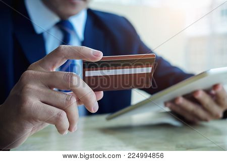 Asian Young Business Man Hands Holding Credit Card And Using Laptop Smart Phone Online Shopping.onli