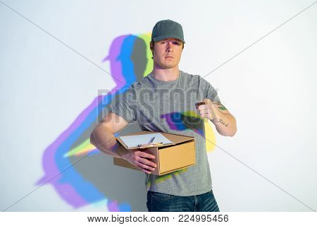 Portrait of reliant man pointing finger in camera. He keeping package with documents. Painted reflection. Conveyance concept