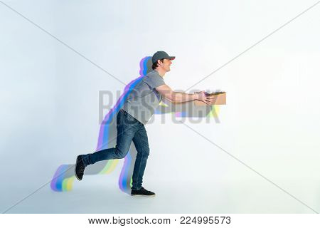 Full length side view laughing courier running with carton box. Multicolored shadow situating on wall. Conveyance concept