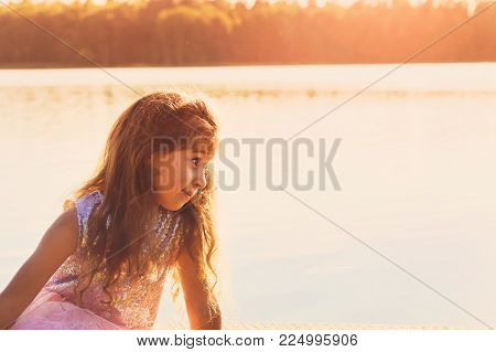 Little girl is looking at the sunset in the seaside