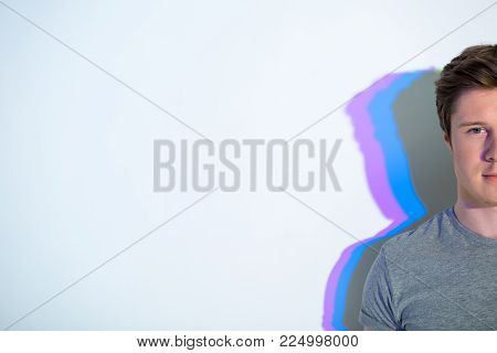 Half face of calm young man standing with multicolored shadow. Copy space. Contemplative concept