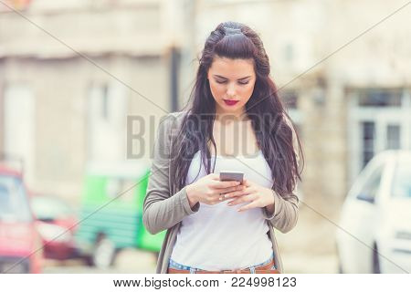 Cute Girl Holding Cellphone In Urban Surroundings. Shallow Focus Is On The Cellphone.