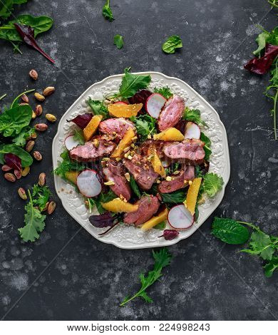 Duck breast fillets steak salad with orange halves, radishes and crushed pistachios.