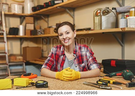 Beautiful smiling caucasian young brown-hair woman in plaid shirt, gray T-shirt, yellow gloves working in carpentry workshop at wooden table place with different men's work tools. Gender equality