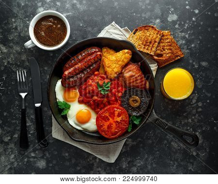 Full English breakfast with bacon, sausage, fried egg, baked beans, hash browns and mushrooms in rustic skillet, pan. cup coffee, orange juice.