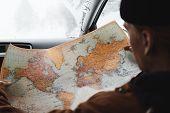 Traveler man sitting inside car and hold vintage world map in hands poster