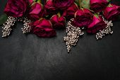 Gothic wedding flowers decor. Dark red or burgundy roses with silver adornment on black background. Bold, daring , alternative , and luxury reception party flower arrangement poster