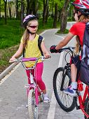 Bikes bicyclist girl. Girls wearing bicycle helmet and glass with rucksack ciclyng bicycle. Walking in spring is good for your health. Bike share program save money and time at city street. poster