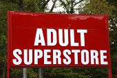 A large red and white sign advertising an Adult Superstore poster