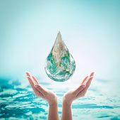 World ocean day, saving water, environmental protection, sustainable ecological ecosystems concept with green earth drop on woman's hands on sea background: Element of this image furnished by NASA poster