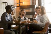 Multiracial friends having fun and laughing drinking coffee in coffeehouse, diverse young people talking joking sitting together at cafe table, multi ethnic millennials spending time in coffee shop poster