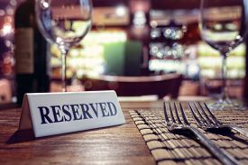 Restaurant reserved table sign with places setting and wine glasses ready for a party
