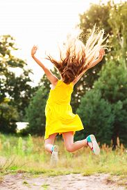 Beautiful teen girl  Is jumping outside at  summer sunset